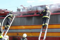 Tűzoltók munkában a füstölő mozdonynál