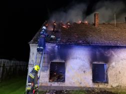Füstölgő ház a háttérben, tűzoltók oltják