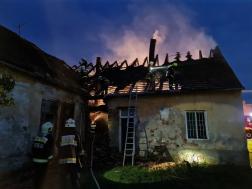 Tűzoltás a háttérben pedig füstöl a tető