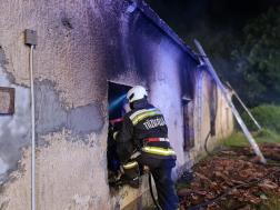 Tűzoltó a kiégett ablakrészen néz be