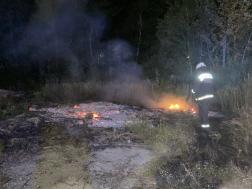 Tűzoltó oltja aszabadtéri tüzet